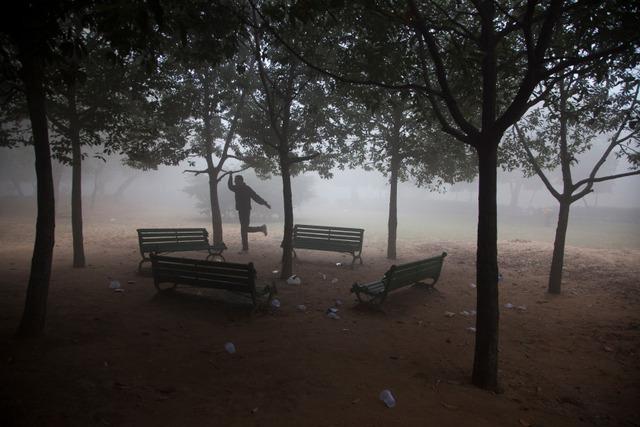 Người đàn ông tập thể dục dưới sương sớm trong một công viên ở New Delhi, Ấn Độ.