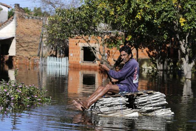 Người đàn ông di chuyển bằng bè trên đường ngập lụt tại thủ đô Asunción, Paraguay.