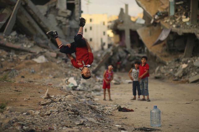 Trẻ em Palestine chơi gần những ngôi nhà bị phá hủy trong cuộc không kích của quân đội Israel nhằm vào thành phố Gaza.
