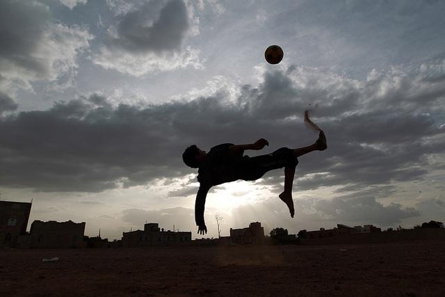 Một cậu bé người Yemen trung người móc bóng trong một trận bóng đá ở thủ đô Sana.
