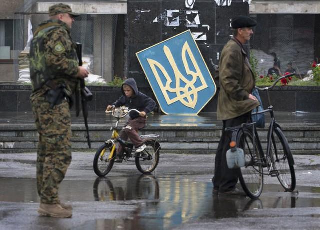 Một cậu bé đạp xe gần binh sĩ Ukraine tại thành phố Slovyansk, vùng  Donetsk.