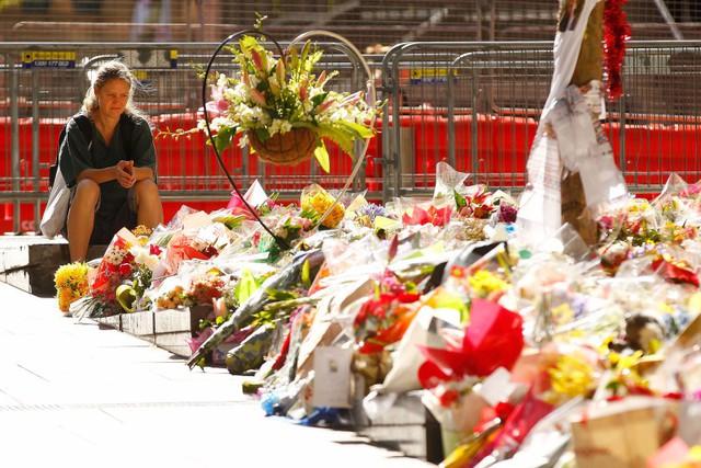 Người phụ nữ ngồi trước khu tưởng niệm những nạn nhân thiệt mạng trong vụ bắt giữ con tin ở Sydney, Australia.