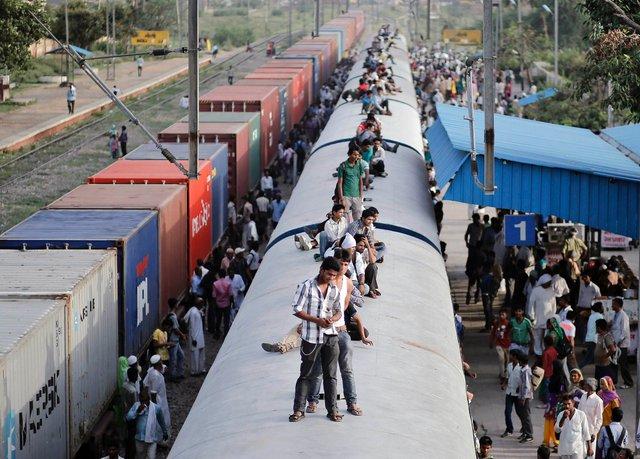 Hành khách trèo lên nóc một đoàn tàu hỏa quá tải tại thị trấn  Loni, bang Uttar Pradesh, Ấn Độ.