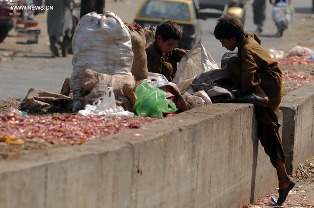 Trẻ em nhặn rau bị bỏ đi tại một khu chợ ở Islamabad, Pakistan.
