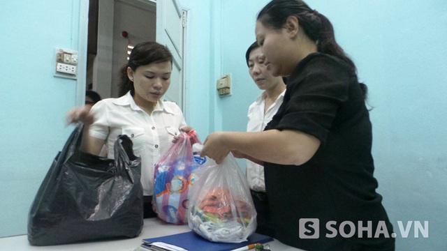 Bà Vũ Yến Oanh - chủ tịch UBND phường 1 cùng các nhân viên khác chuẩn bị quần áo cho cháu bé