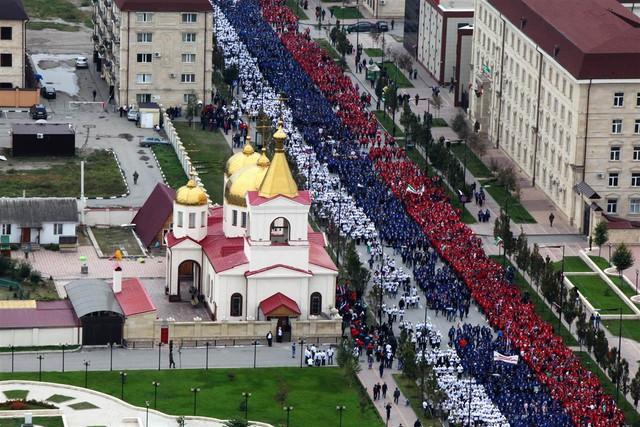 Dân chúng diễu hành theo hình quốc kỳ Nga tại Grozny, Nga để chúc mừng sinh nhật Tổng thống Putin ngày hôm qua.