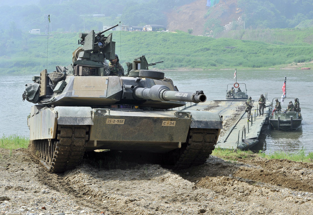 A US M1A2 tank crosses a river by a South Korean military barge duirng a US-South Korea joint river crossing exercise in the border city of Yeoncheon, northeast of Seoul, on May 30, 2013