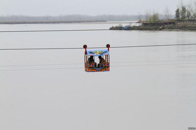 Những người đàn ông ngồi trên ghế treo để qua sông ở Charsadda, gần Peshawar, Pakistan.