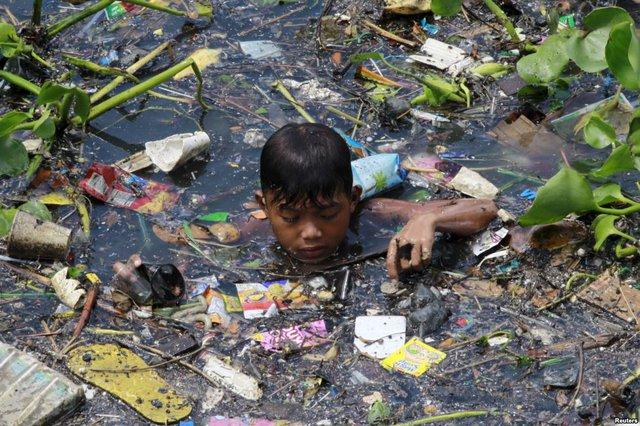 Cậu bé thu lượm những đồ có thể tái chế dưới một dòng sông gần thành phố Navotas, Philippines.