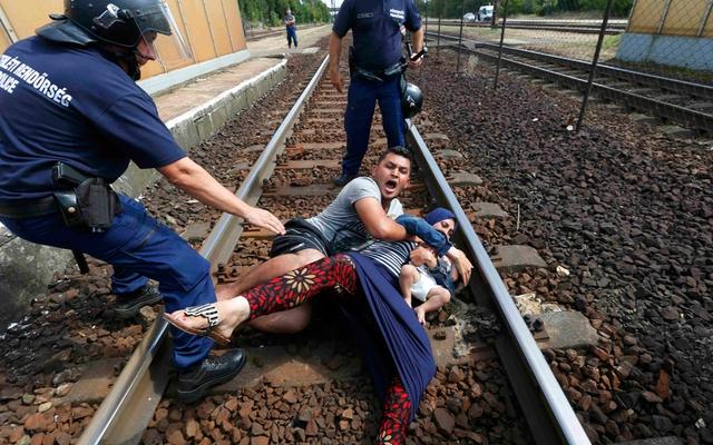 Người đàn ông di cư ôm vợ và con nằm giữa đường ray ở Hungary để phản đối việc cảnh sát đưa họ tới trại tị nạn thay vì đến biên giới Áo như kế hoạch.