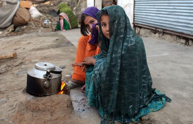 Các bé gái tị nạn sưởi ấm bên bếp lò tại khu định cư tạm ở tỉnh Nangarhar, Afghanistan.