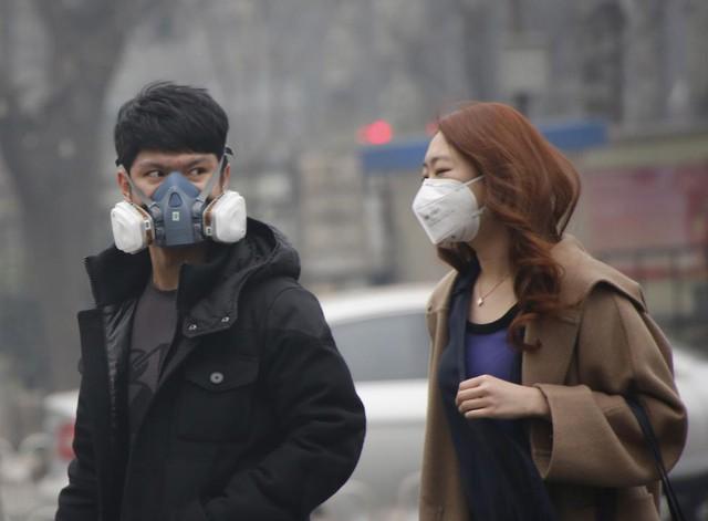 Một cặp đôi đeo khẩu trang kín mít để tránh hít phải không khí ô nhiễm trong ngày Bắc Kinh phát báo động đỏ về ô nhiễm ngày 8.12.