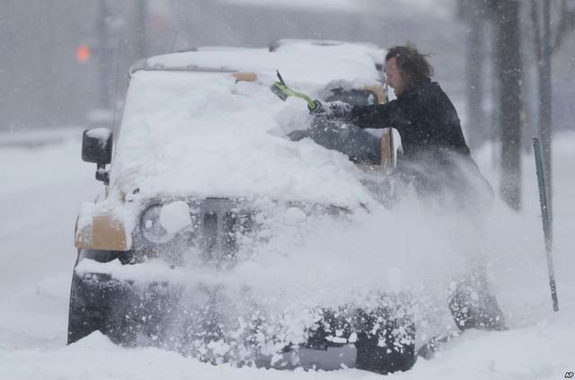 Người đàn ông dọn lớp tuyết dày phủ kín chiếc ô tô của mình trên đường phố ở Denver, bang Colorado, Mỹ.