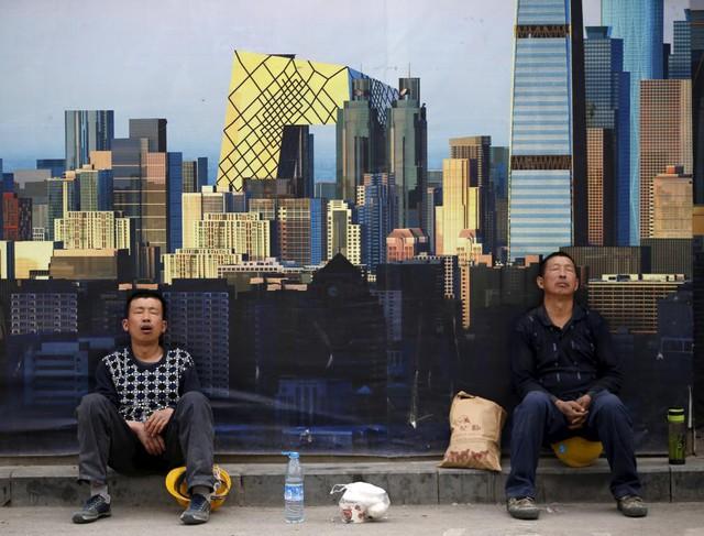 Công nhân tranh thủ ngủ trưa trước bức tưởng của một công trường xây dựng ở thành phố Bắc Kinh, Trung Quốc.