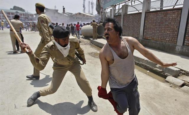Cảnh sát dùng gậy để giải tán người biểu tình ở Srinagar, Ấn Độ.