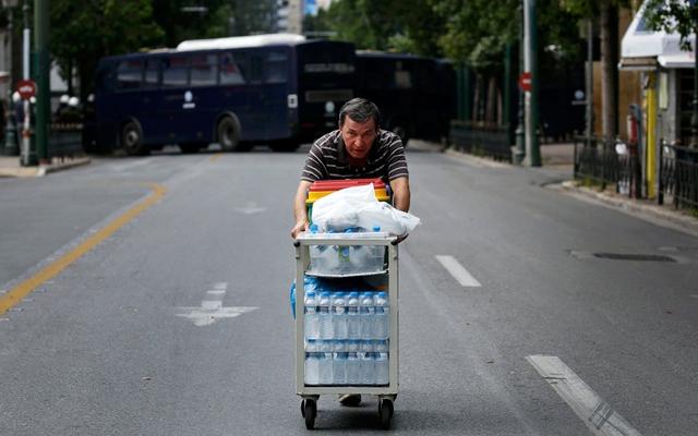 Người đàn ông đẩy xe bán nước trên đường phố vắng tanh ở thủ đô Athens, Hi Lạp.