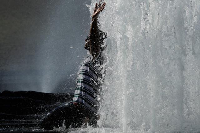 Người đàn ông tắm mát trong một đài phun nước ở Berlin, Đức.