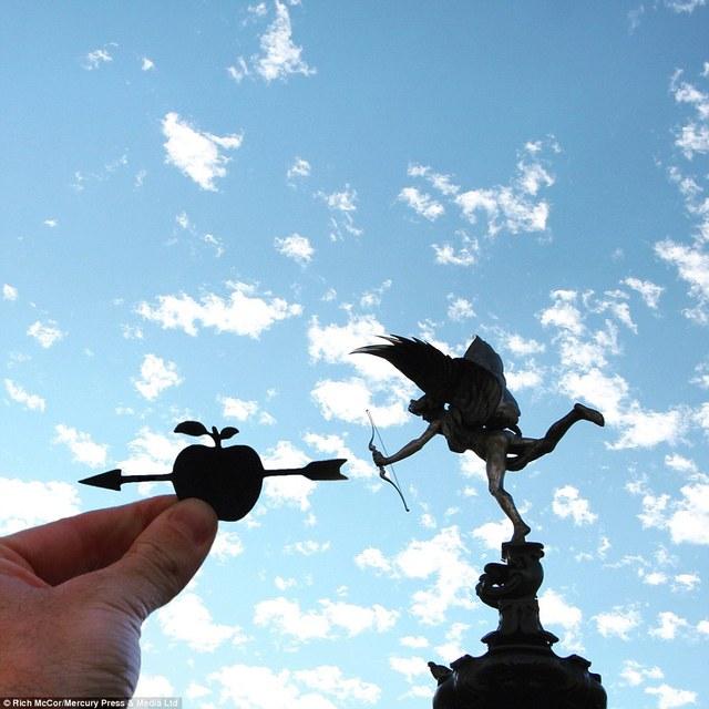 Hình cắt mũi tên xuyên qua quả táo được đặt cạnh bức tượng giữa ngã tư Piccadilly Circus.