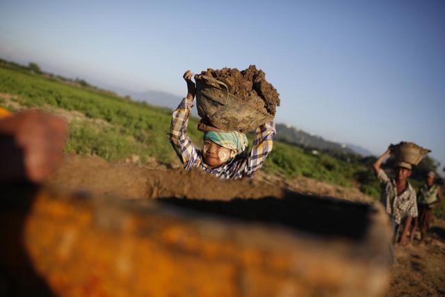 Cậu bé 11 tuổi đội đất trên đầu khi làm việc tại một nhà máy sản xuất gạch ở thành phố Mandalay, Myanmar.