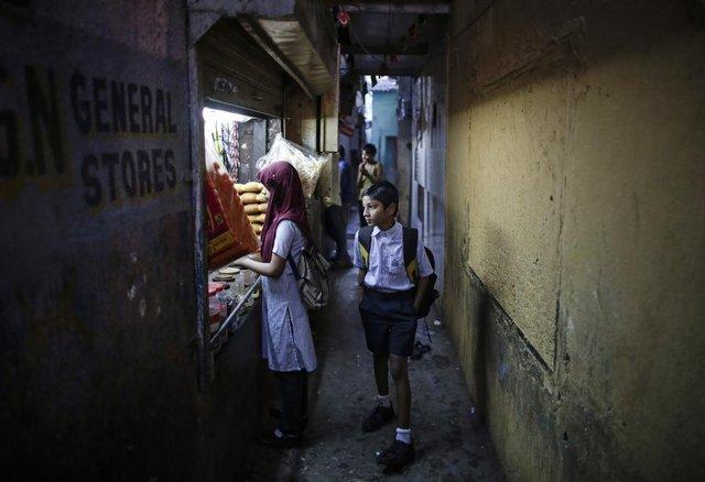 Cậu học sinh đi qua ngõ nhỏ tại một khu ổ chuột ở Mumbai, Ấn Độ.