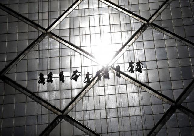 Công nhân lau những tấm kính trên một tòa nhà chọc trời ở Bắc Kinh, Trung Quốc.