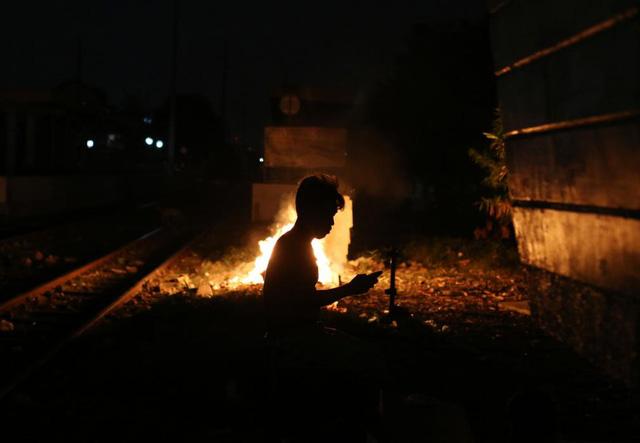 Một cậu bé dùng điện thoại cạnh đống lửa dọc đường ray tàu hỏa ở Manila, Philippines.