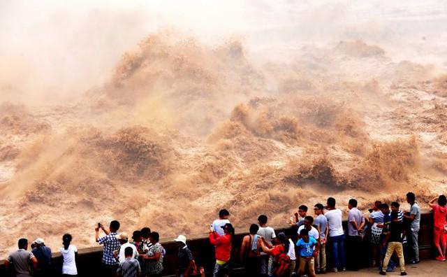 Du khách xem cảnh xả bùn đất từ đập Xiaolangdi trên sông Hoàng Hà tại tỉnh Hà Nam, Trung Quốc.