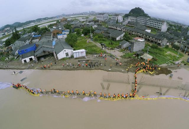 Quân đội và người dân ở tỉnh Chiết Giang, Trung Quốc, xếp bao tải cát làm để chắn nước lũ sau khi một đập bị vỡ do ảnh hưởng bởi siêu bão Soudelor.