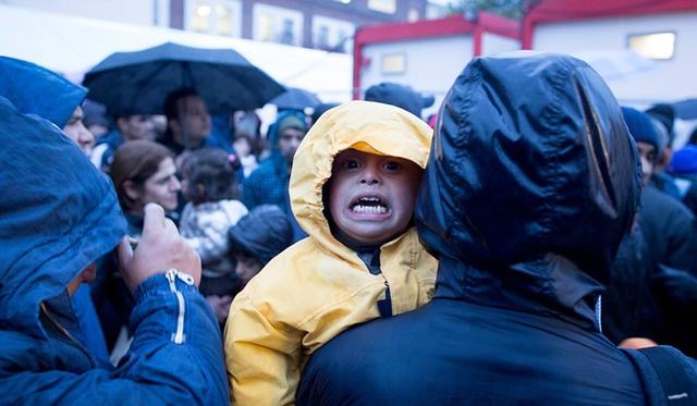 Em bé di cư khóc vì lạnh khi chờ đăng ký tị nạn dười trời mưa rét ỏ Berlin, Đức.