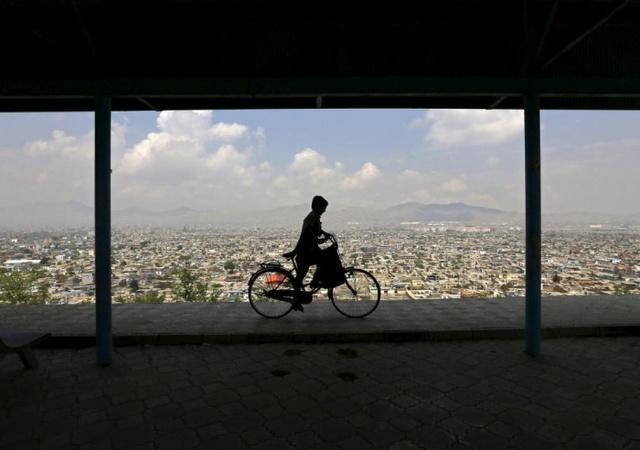 Cậu bé đạp xe trên đỉnh đồi nhìn xuống thành phố Kabul, Afghanistan.