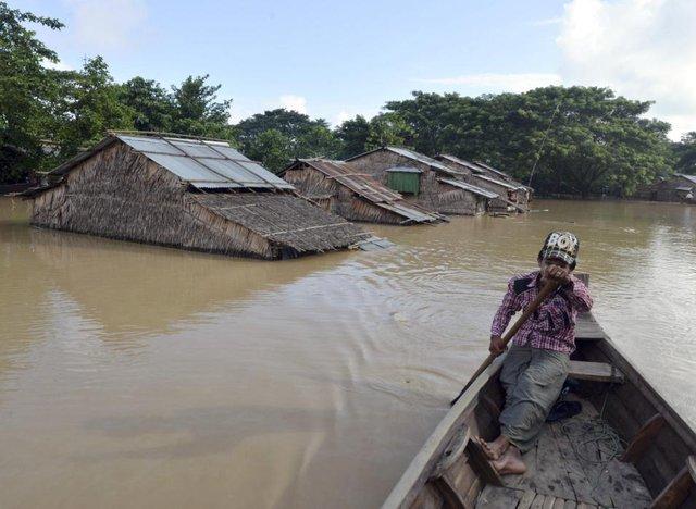 Cậu bé chèo thuyền tại khu dân cư ngập trong nước lũ ở vùng đồng bằng Ayeyarwaddy, Myanmar.