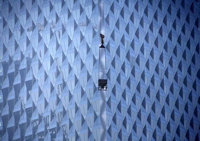 Cần cẩu hoạt động tại một công trường xây dựng tòa nhà thương mại mới ở Bắc Kinh, Trung Quốc.