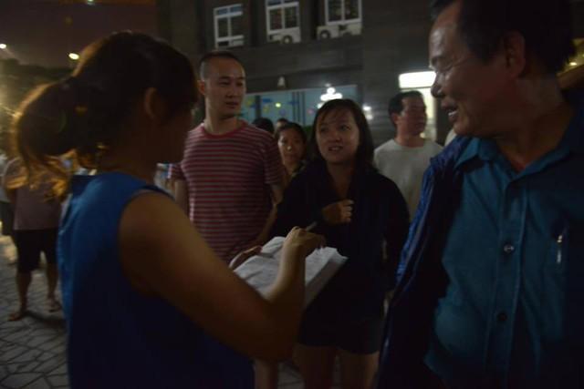 Bà Hà, một thành viên của tổ dân phố đang đi ghi lại danh sách các hộ dân ở từng tầng. Ảnh: Hoàng Anh.