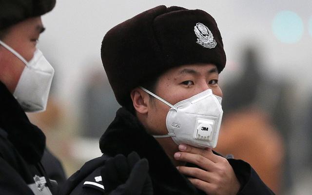 Viên cảnh sát điều chỉnh khẩu trang lọc không khí trong khi làm nhiệm vụ cùng đồng nghiệp ở Thiên An Môn.