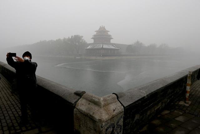 Du khách đeo khẩu trang kín mít chụp ảnh tự sướng bên cạnh một tòa lầu ở Tử Cấm Thành.
