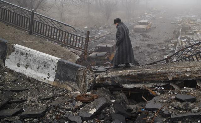 Người phụ nữ đi qua cây cầu bị sập do giao tranh ở Donetsk, Ukraine.