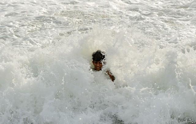 Một cậu bé thích thú vui đùa với sóng nước tại bãi biển ở Colombo, Sri Lanka.