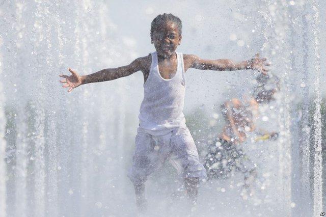 Trẻ em thích thú chơi trong đài phun nước vào một ngày nắng nóng ở Cincinnati, Ohio, Mỹ.