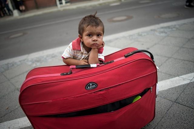 Em bé di cư ngồi chờ bên cạnh chiếc vali khi bố mẹ cậu đang xin giấy phép tị nạn tại văn phòng Các vấn đề y tế và xã hội ở Berlin, Đức.