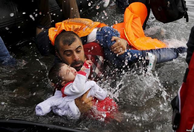 Người di cư Syria bế con trong khi nhảy khỏi thuyền để vào bờ trên đảo Lesbos, Hi Lạp.