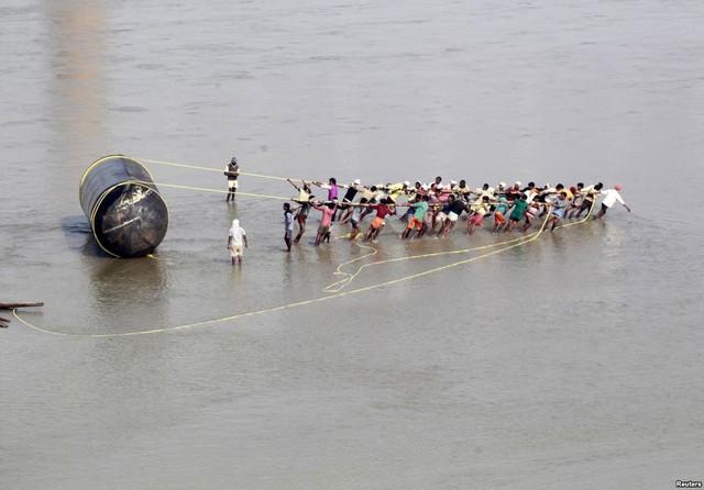 Người lao động kéo một thùng lặn để xây dựng cầu tạm qua sông Hằng nhằm phục vụ cho lễ hội Magh Mela ở Allahabad, Ấn Độ.