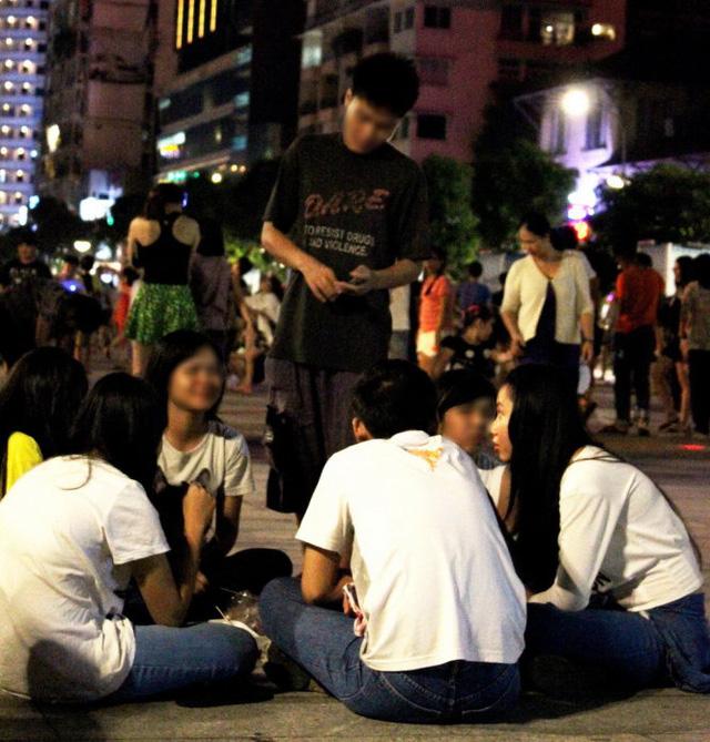 Đối tượng đang tiếp cận một nhóm bạn tại phố đi bộ Nguyễn Huệ tối 12-7. Ảnh: Mạnh Khang