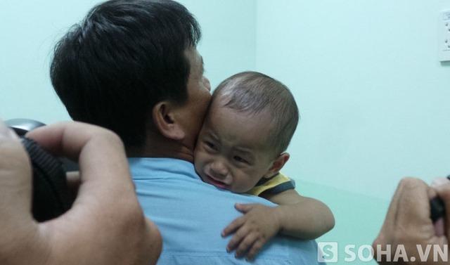 Dù được cha và các bác sĩ cưng nựng nhưng bé Huy vẫn mếu máo