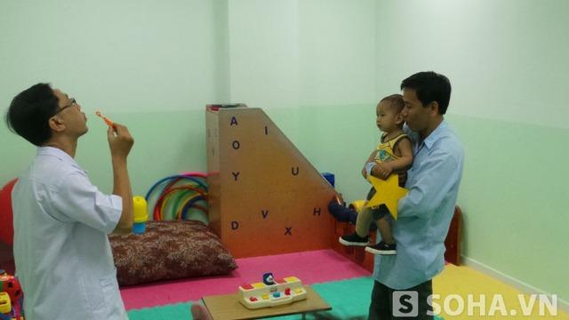 Vài phút sau, bé bắt đầu quen và chăm chú theo dõi bác sĩ hướng dẫn cách chơi