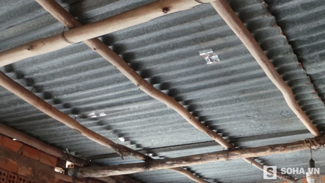 Nhiều lỗ thủng được dán băng keo lại trên mái nhà ông Nén