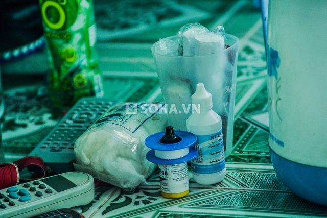 Trên sàn nhà Phùng Ngọc bày la liệt bông và thuốc y tế để tiện vệ sinh cho ngón tay đang bị nhiễm trùng nặng.