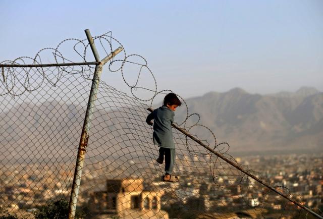 Cậu bé treo lên hàng rào sắt trong khi chơi đùa ở thành phố Kabul, Afghanistan.