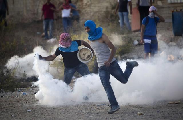 Người biểu tình Palestine ném lựu đạn hơi cay trở lại binh sĩ Israel trong cuộc đụng độ gần thành phố Ramallah, Bờ Tây.