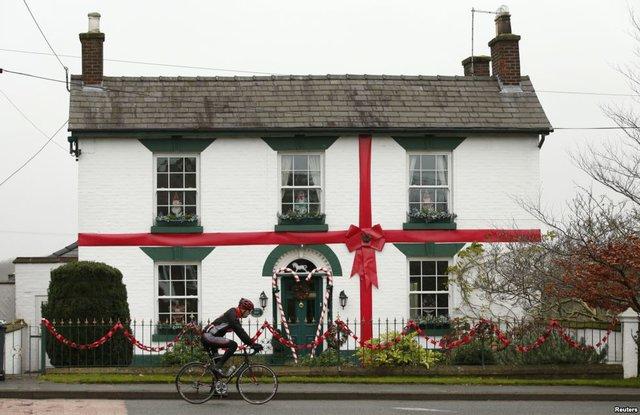 Người đàn ông đạp xe qua ngôi nhà được trang trí như món quà Giáng sinh ở Scholar Green, Anh.