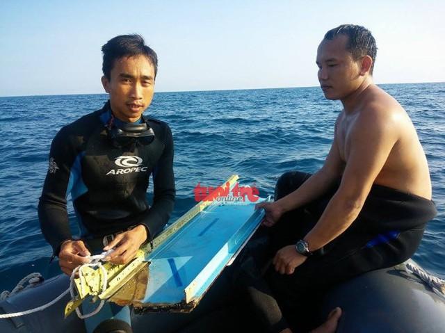 Hai chiến sĩ vừa đưa mảnh vỡ máy bay Su-22 lên từ lòng biển - Ảnh: HOÀNG VĂN SỐ